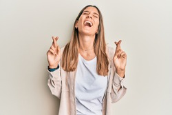 Brunette young woman doing fingers crossed gesture smiling and laughing hard out loud because funny crazy joke.