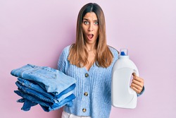 Brunette young woman holding jeans for laundry and detergent bottle afraid and shocked with surprise and amazed expression, fear and excited face.