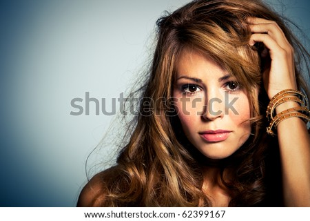 brunette young woman portrait with hand in hair studio shot