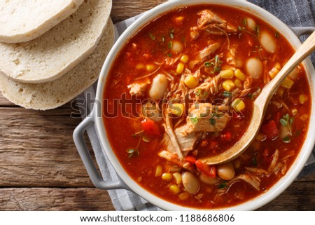 Brunswick Stew - thick, flavorful and hearty one-pot stew with vegetables and meat on a chicken broth and BBQ sauce close-up in a bowl on the table. Horizontal top view from above