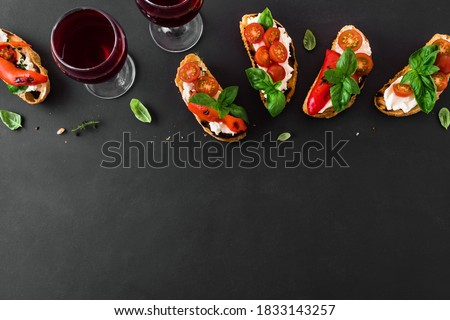Bruschetta sandwiches with tomatoes, cream cheese, grilled paprika and basil on dark background, top view, copy space. Traditional italian snack for wine - grilled bruschetta toasts. Stock fotó ©