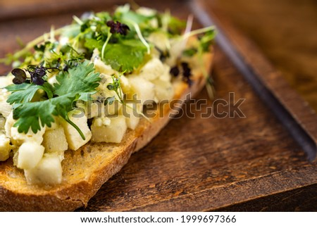 bruschetta with cheese and greens on a wooden cutting board for photos and video shooting. work as a food stylist and photographer. restaurant menu and kafe Stok fotoğraf ©