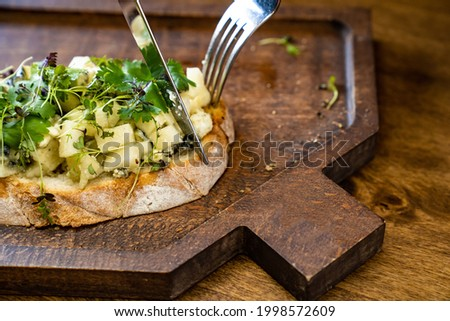 bruschetta with cheese and greens on a wooden cutting board with a knife and a folk for photos and video shooting. work as a food stylist and photographer. restaurant menu and kafe Stok fotoğraf ©