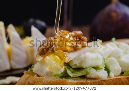 bruschetta with cheese, fruit and nuts is drizzled with honey. macro