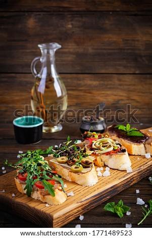 Bruschetta with chicken liver paste. Delicious bruschettas with various fillings. Different bruschetta ob wooden background Stock fotó ©