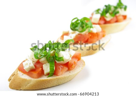 Bruschetta with fresh diced tomatoes, mozzarella and fresh basil isolated on white - Shallow DOF