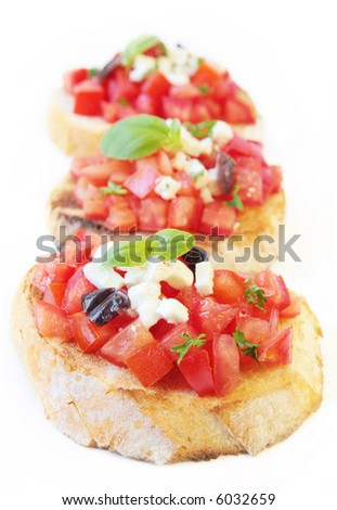 Bruschetta with fresh vine tomatoes, olives, fetta cheese, and basil, on crostini.  Shallow DOF.