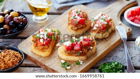 Bruschetta with olive tapenade and fresh tomatoes on cutting board. Wooden background. Close up. Stock fotó ©