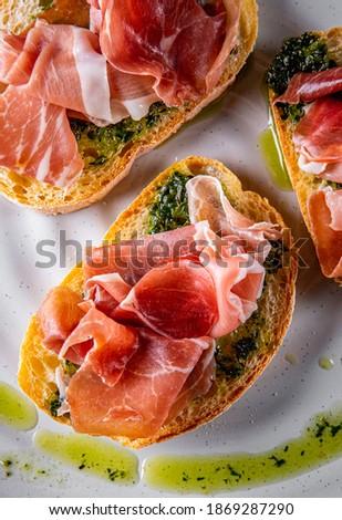 Bruschetta with prosciutto and pesto sauce on plate Foto stock ©
