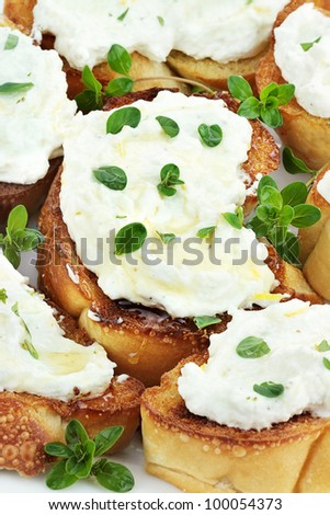 Bruschetta with ricotta cheese, lemon zest and thyme, drizzled with golden honey.  Shallow depth of field.