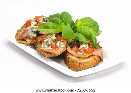 bruschetta with tomatoes and gorgonzola cheese served with fresh basil on white plate