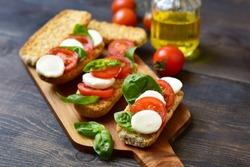 bruschetta with tomatoes, mozzarella and Basil, Caprese salad on toast. typical Italian antipasti starter in a restaurant in Italy Rome Milan. tomato bruschetta recipe, selective focus
