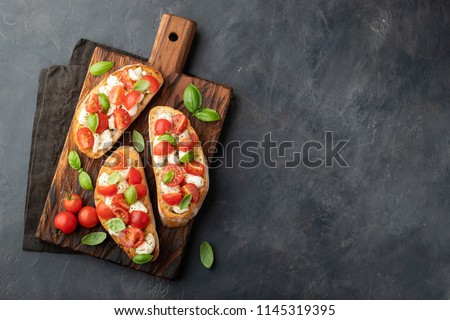 Bruschetta with tomatoes, mozzarella cheese and basil on a cutting board. Traditional italian appetizer or snack, antipasto. Top view with copy space. Flat lay Stock fotó ©