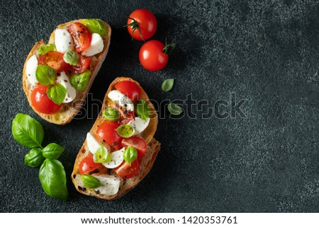 Bruschetta with tomatoes, mozzarella cheese and basil on a dark background. Traditional italian appetizer or snack, antipasto. Top view with copy space. Flat lay Сток-фото ©