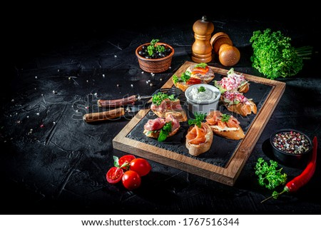 Bruschetta with tomatoes, mozzarella cheese and basil on dark background. Traditional italian appetizer or snack, antipasto Stock fotó ©