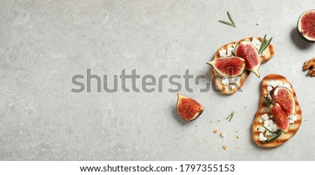 Bruschettas with figs and cheese on light table, flat lay. Space for text, banner design  Stock fotó ©