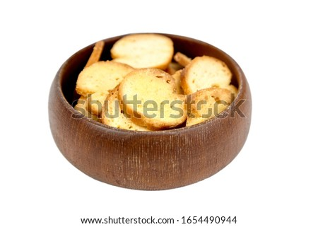 Bruschette chips, dry slices of baked bread, beer snacks in wooden bowl, isolated on white background, selective focus