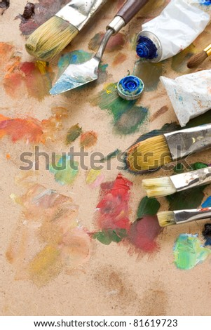 brush and art palette with paints on wood