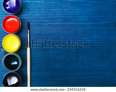 Brush and paint for painting. Liquid paint on a background of blue wooden surface