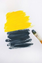Brush for painting on the background of abstract gouache paintings in yellow and gray colors. Brushstrokes on canvas. Color 2021.