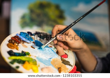 Brush in hand. Oil painting. Beatiful picture. Palette paint.