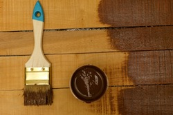 Brush on wooden background. Board half painted. painting of wooden yellow boards in brown color