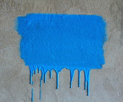 Brush strokes and paint drips on the concrete wall