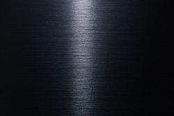Brushed metal texture in the dark with narrow lighting in middle.