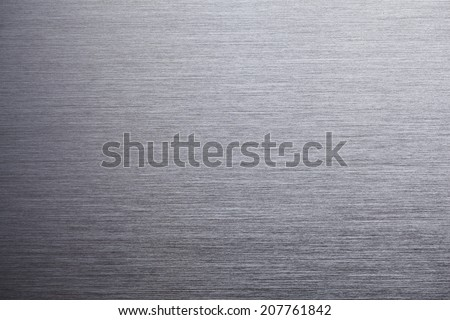 Brushed metal texture, shadow on lower left.
