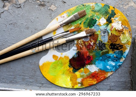 Brushes and colorful abstract oil colors painters pallet, on retro background