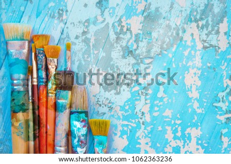 Brushes artist on a wooden table. Bright artistic background. #1062363236