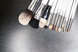Brushes for make-up with a white plastic handle isolated on a black background or lie on the surface of the table.