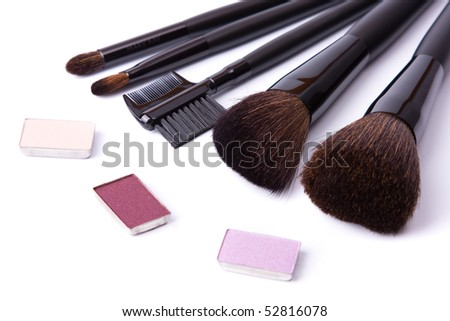 Brushes to make-up and collection of eye shadow on white background