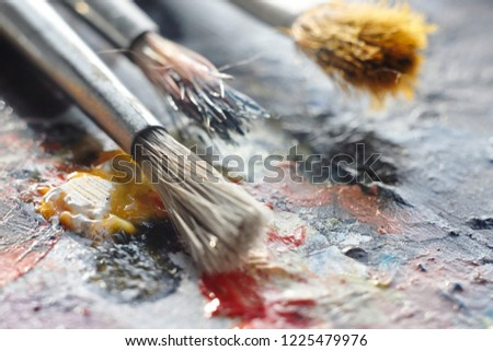 brushes with a bristle brush lying on the palette with oil  #1225479976