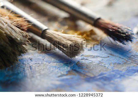 brushes with bristles on the palette with oil  #1228945372