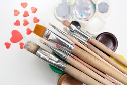 Brushes with colorful paints on a background with hearts and a palette.