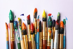 Brushes with colorful paints on white background, flat lay