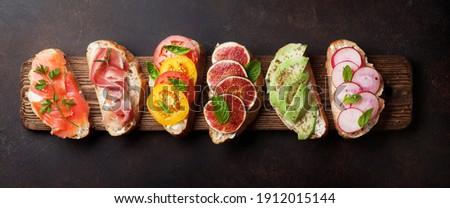 Brushetta or traditional spanish tapas. Appetizers italian antipasti snacks set on wooden board. Top view flat lay Foto stock ©