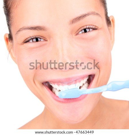 Brushing teeth. Closeup of woman brushing her teeth with toothpaste and a manual toothbrush. Beautiful mixed race asian / caucasian model.