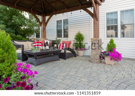 Brussel block design pavers on an exterior patio and summer living space with a covered gazebo, colorful petunias and comfortable seating