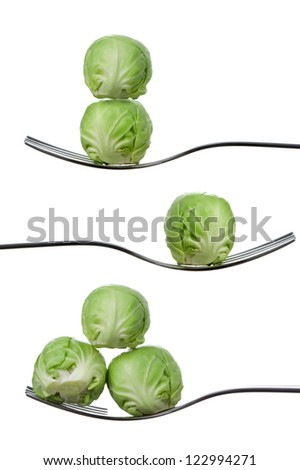 brussel sprouts balancing on forks against a white background