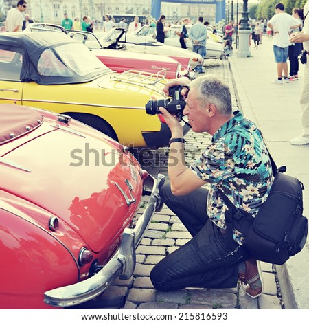 stock-photo-brussels-belgium-september-tourist-takes-a-picture-of-a-vintage-car-exposed-during-comic-215816593.jpg