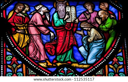 BRUSSELS - JULY 26: Stained glass window depicting Moses and the Stone Tablets with the Ten Commandments in the cathedral of Brussels on July, 26, 2012. - stock photo