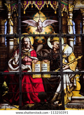 BRUSSELS - JULY 26: Stained glass window depicting the Holy Trinity (Father, Son and Holy Spirit) in the cathedral of Brussels on July, 26, 2012.