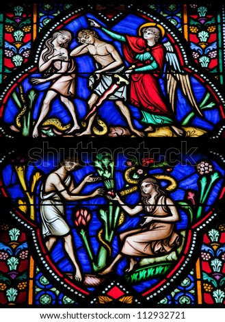 BRUSSELS - JULY 26: Stained glass window depicts Adam and Eve eating the Forbidden Fruit and being expelled from the Garden of Eden in the cathedral of Brussels on July, 26, 2012.