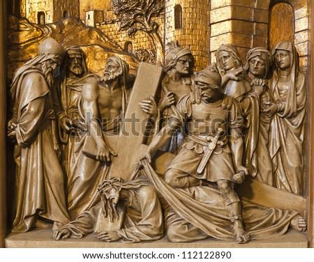 BRUSSELS - JUNE 24: Jesus falls under cross. Relief from Cross way in Saint Antoine church on June 24, 2012 in Brussels.