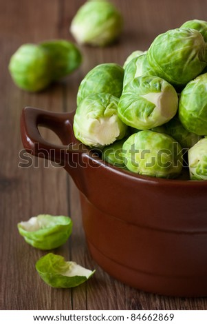 Brussels sprouts in a brown ceramic saucepan close-up.