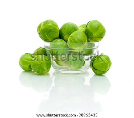 Brussels sprouts in a glass bowl closeup on a white background with reflection