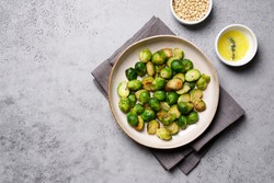 Brussels sprouts roasted with butter on gray slate background. Vegan Food Concept. Copy space, top view, flat lay