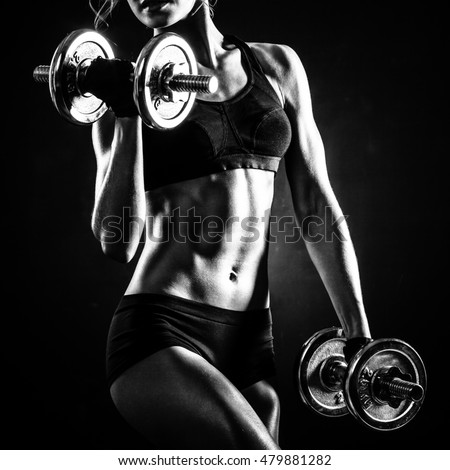 Stock Photo Brutal athletic woman pumping up muscles with dumbbells
